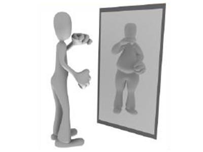 Eine schmale Figur vor dem Spiegel.