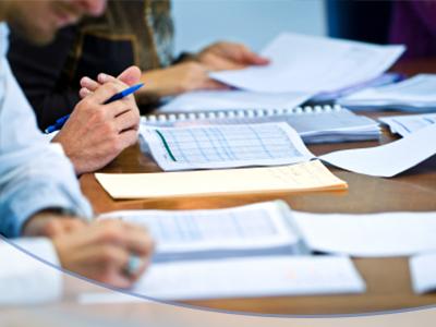 Menschen sitzen am Schreibtisch und schreiben