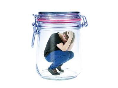 Ein Mann hockt in einem Einmachglas